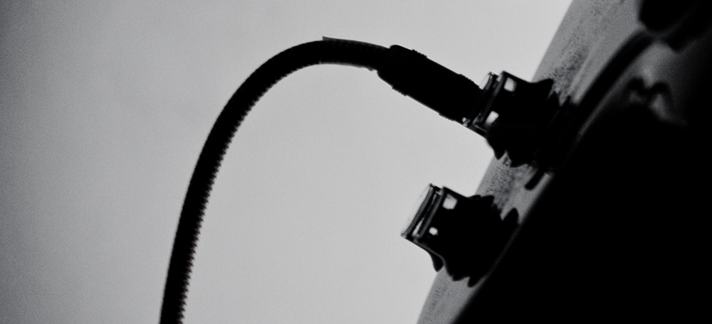 Photograph of cord plugged into amp in black and white