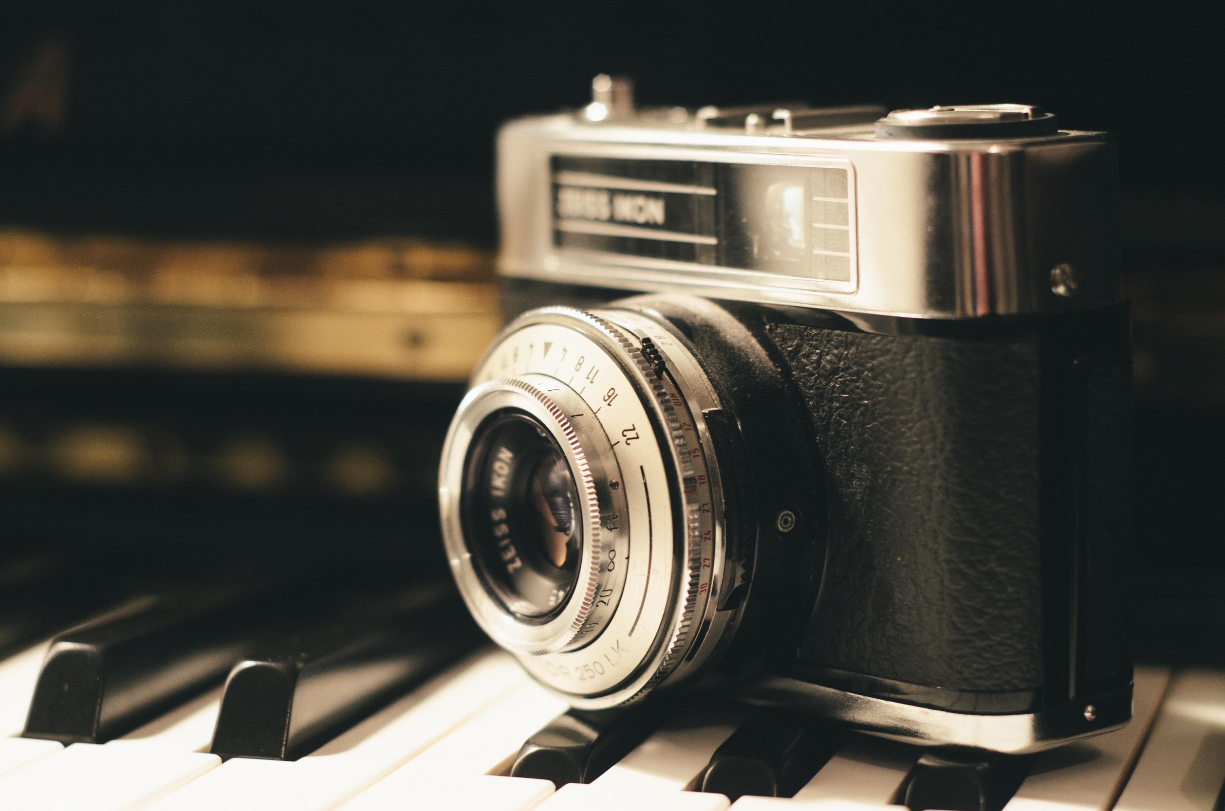 Photograph of 35mm camera on piano keys