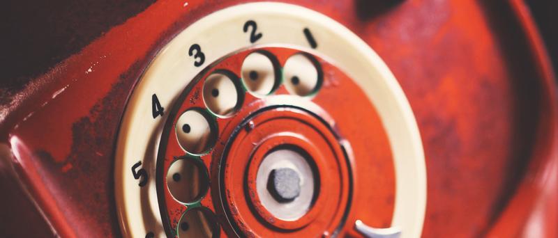 Photo of closeup of red rotary telephone