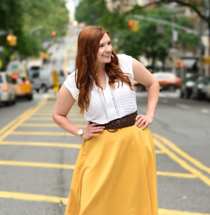 Woman posing in street with hands on hips looking away from camera and smiling while wearing yellow skirt and white shirt